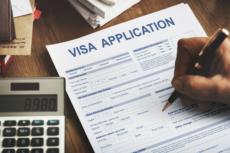 Canadian man filling in a visa application form with calculator on desk